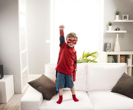 antifaz de carnaval: El niño pequeño superhéroe de pie en el sofá y que presenta como un verdadero héroe. Foto de archivo