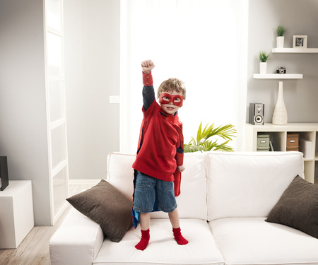 cool kids: Little superhero boy standing on sofa and posing like a real hero.