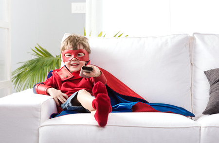 Cute boy with super hero costume sitting on living room sofa and watching tv.