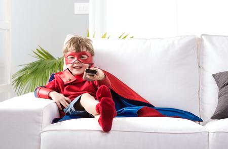 personas viendo television: Muchacho lindo con el traje de s�per h�roe sentado en sof� de la sala y viendo la televisi�n. Foto de archivo