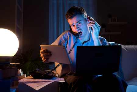 man confused: Stressed businessman working overtime late at night in the living room with telephone, computer and tablet.