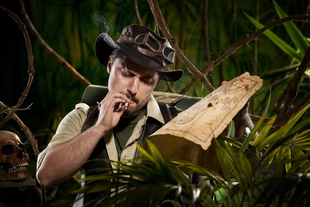 Lost explorer in the jungle holding an old map and smoking a cigarette. photo