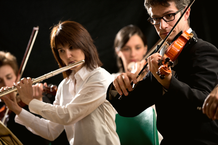 musical instrument: Female flutist and violinist performing in classical music concert.