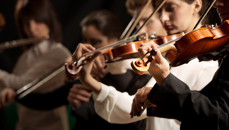 musical instrument: Symphony orchestra violinists performing on stage against dark background. Stock Photo