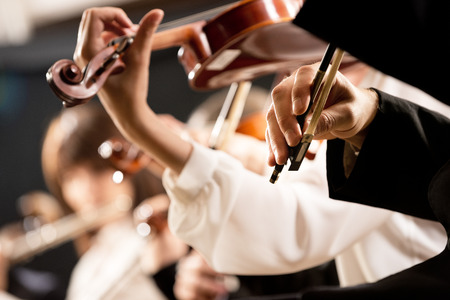 Elegant violin players, hands close-up and orchestra on background.
