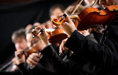 Symfonický orchestr první housle část předvádění na tmavém pozadí.