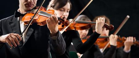 ヴァイオリン オーケストラ暗い背景にステージで演奏します。