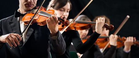 violin: Violin orchestra performing on stage on dark background.