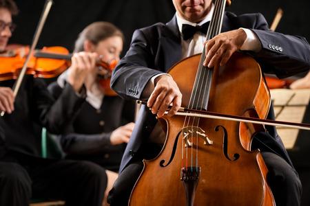 Cello professionele speler met symfonisch orkest uitvoeren in concert op de achtergrond.