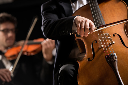 Cello professional player with symphony orchestra performing in concert on background. photo
