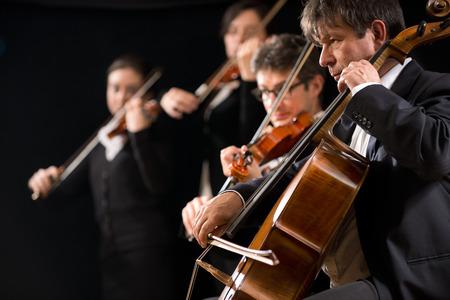 Strijkorkest presteren op het podium met de cello op de voorgrond.