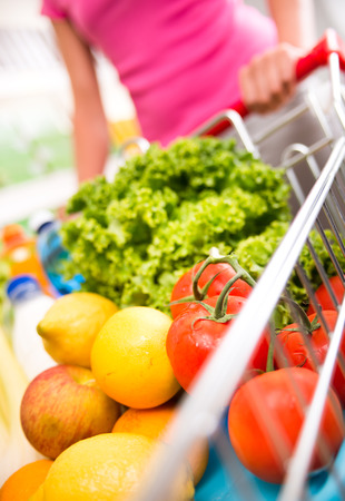 food shelf: Woman at supermarket pushing a shopping cart filled with fresh fruit and vegetables. Stock Photo