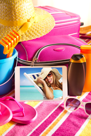 Tablet showing vacations pictures with towel, sunglasses, sun creams and beach accessories. photo