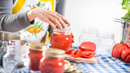 Woman filling glass jars with tomato sauce on checked tablecloth, hands close-up. photo