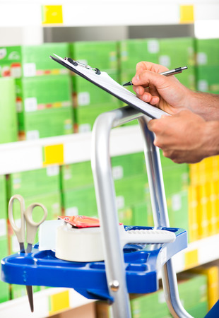 manual worker: Supermarket clerk at work holding pen and clipboard with shelf on background, hands close-up.