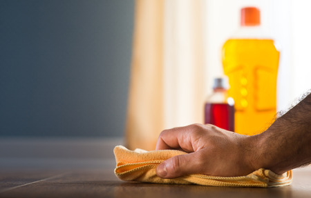 disinfecting: Male hand applying wood care products and cleaners on hardwood floor surface.