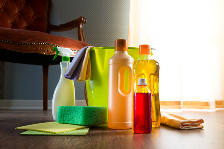 cleaning products: Wood cleaners with bucket, gloves and sponge on living room hardwood floor. Stock Photo