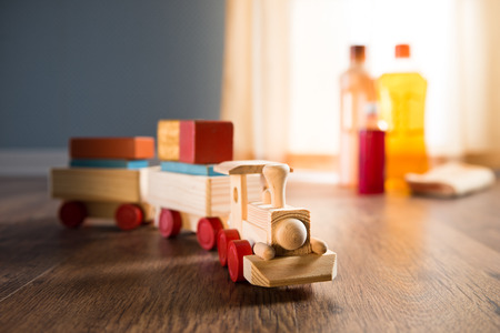 disinfecting: Wooden toy train with wood cleaner products on parquet next to a window.