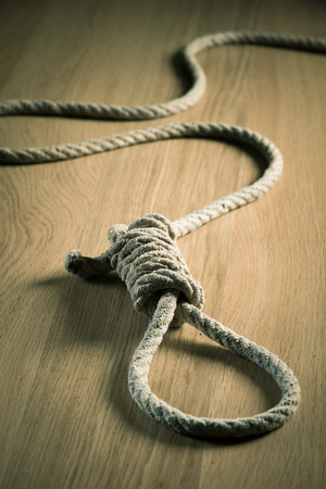 gallow: Noose lying on hardwood floor, suicide and punishment concept.