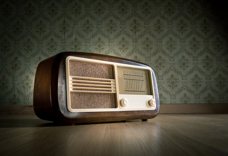 shortwave: Old vintage radio on hardwood floor with retro wallpaper on background.
