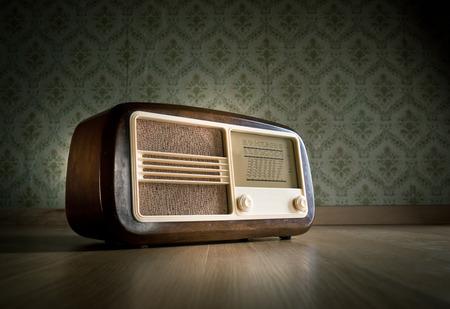Vieille radio vintage sur plancher de bois franc avec du papier peint rétro sur fond. Banque d'images - 30940319
