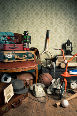 Assorted vintage items in the attic with retro wallpaper background. Stock Photo