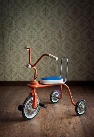 Vintage orange tricycle on hardwood floor and vintage wallpaper on background. photo