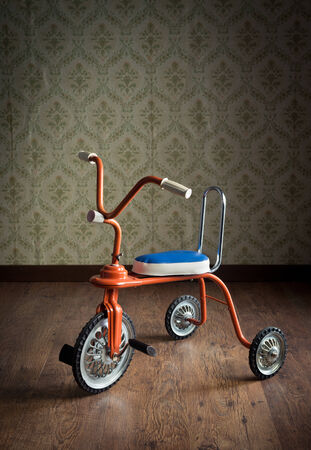antique tricycle: Vintage orange tricycle on hardwood floor and vintage wallpaper on background.