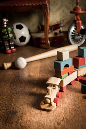 toy train: Wooden train and vintage colorful toys on hardwood floor and retro wallpaper on background.