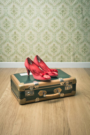 old shoes: Female red dotted shoes with vintage suitcase on floor and retro wallpaper. Stock Photo