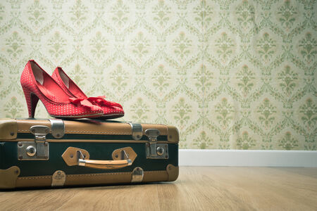 red shoes: Female red dotted shoes with vintage suitcase on floor and retro wallpaper. Stock Photo