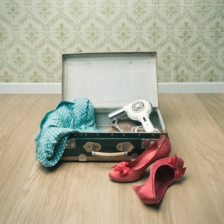Open vintage suitcase with red shoes and dotted clothing, retro wallpaper on background. photo