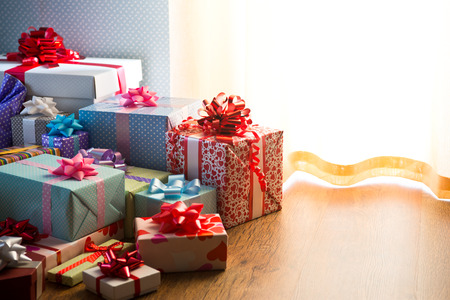 Plenty of colorful wrapped christmas presents on the floor next to the window. photo