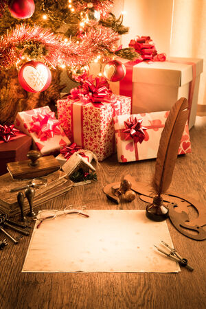 Old letter with feather pen and glasses, gifts and christmas tree on background. photo