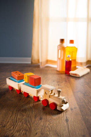 toy train: Wooden toy train with wood cleaner products on parquet next to a window.