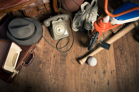 Group of assorted vintage items on hardwood floor at flea market. Stockfoto