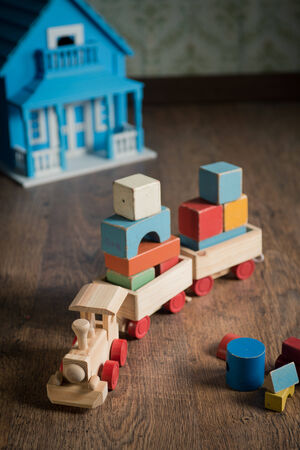 doll house: Wooden train and doll house on the floor with vintage wallpaper on background.