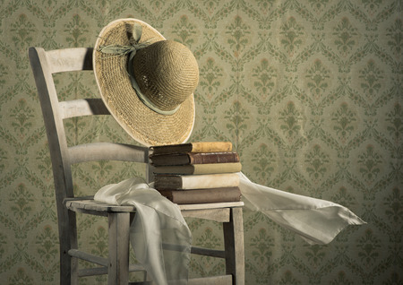 vintage chair: Stack of ancient books on a chair with straw hat and headscarf, vintage wallpaper on background. Stock Photo
