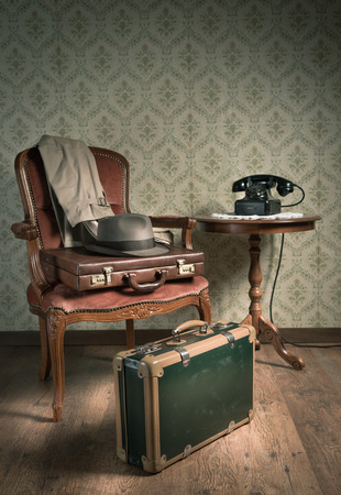 Male hat and suitcases on elegant armchair in a vintage style room. photo