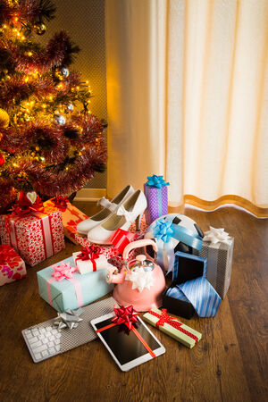 Christmas gifts for all family under decorated tree with lights and colorful baubles. photo