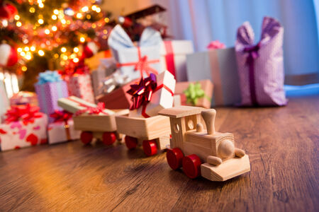 Wooden toy train with special gift and christmas tree on background. photo