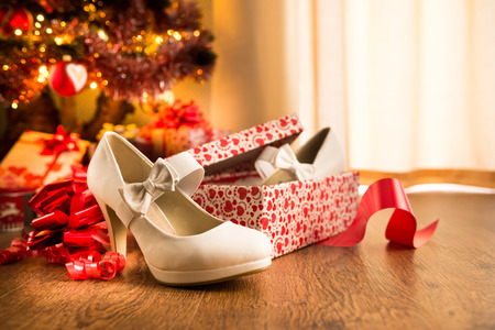White female elegant shoes in a gift box with christmas tree and presents on background. photo
