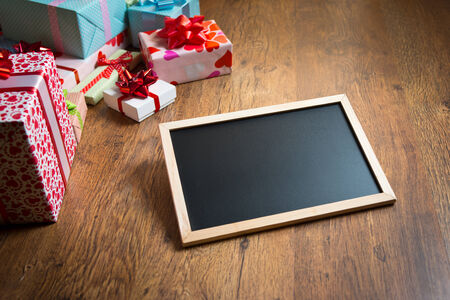 beautifully wrapped: Beautifully wrapped gifts with blank blackboard on wooden surface. Stock Photo