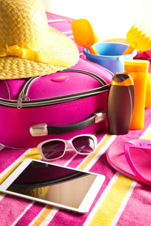 pink hat: Empty touch screen tablet with colorful beach towel, sunglasses, sun creams and beach accessories. Stock Photo