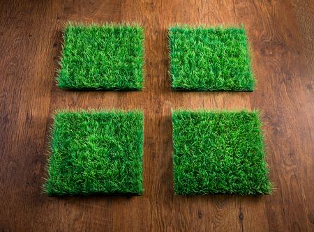pasto sintetico: Cuatro azulejos de césped artificial en el suelo de la madera dura, el concepto del cuidado del medio ambiente.