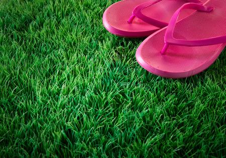 pasto sintetico: Flip flops rosa en la verde hierba artificial exuberante, verano y vacaciones concepto. Foto de archivo