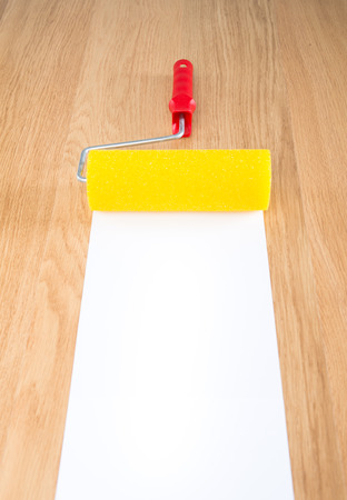 red paint roller: Yellow and red paint roller on hardwood floor with white copyspace paint.