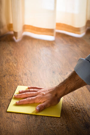 floor cloth: Male hand cleaning and rubbing an hardwood floor with a microfiber cloth. Stock Photo