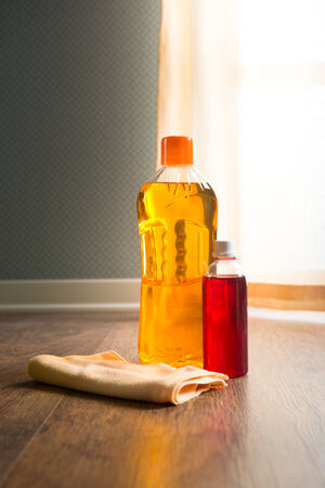 disinfecting: Hardwood floor mantainance products on parquet with microfiber cloth.