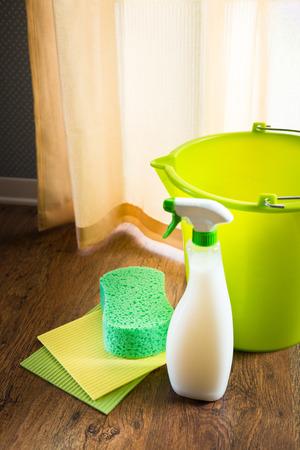 disinfecting: Spray detergent with green bucket, sponge and pads on living room hardwood floor. Stock Photo